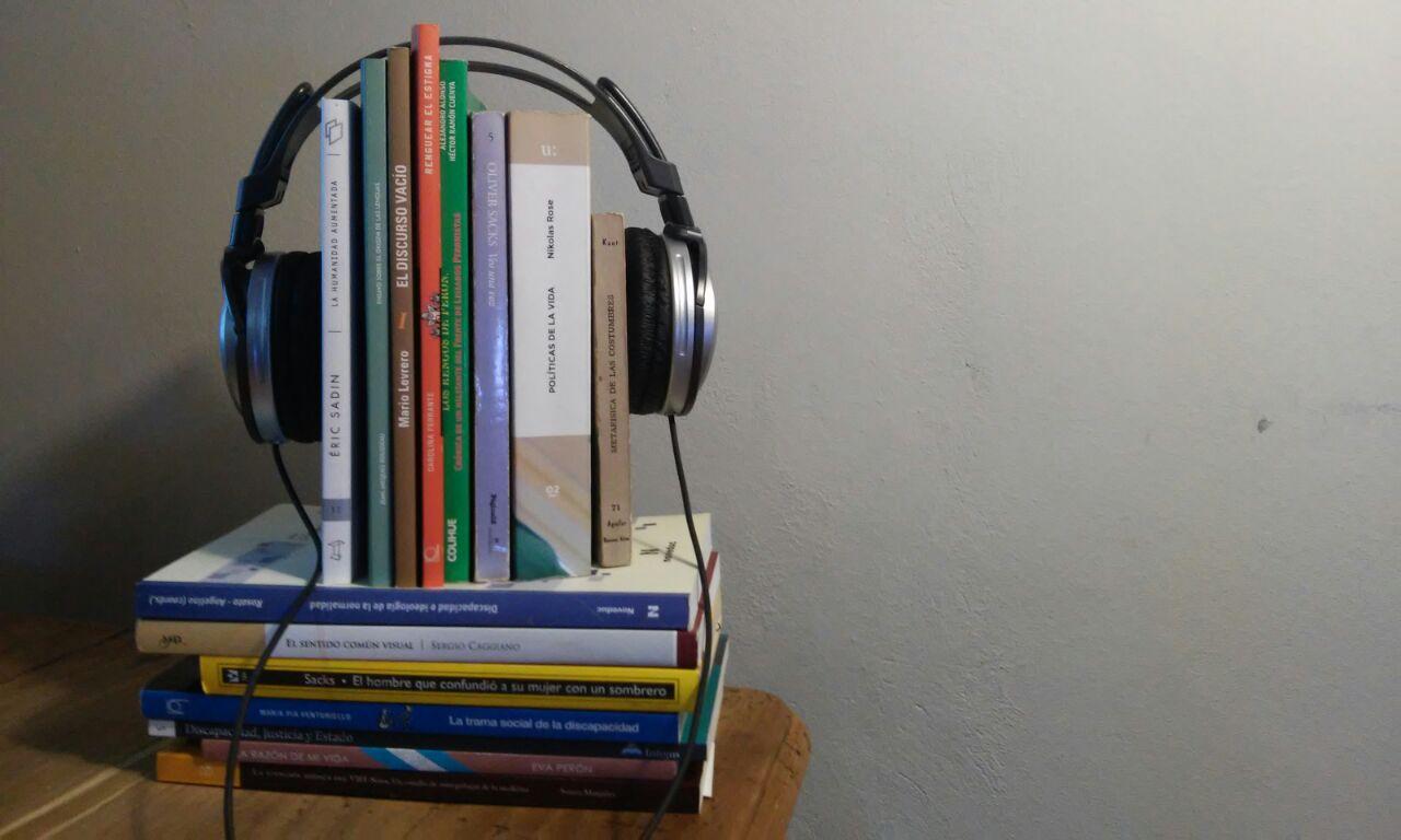 La imagen muestra un grupo de libros con unos auriculares puestos, aludiendo a los audiolibros accesibles.