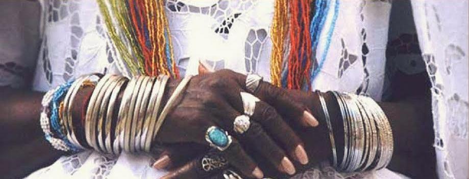 La imagen muestra ambas manos de una persona africana apoyadas una sobre otra, con anillos y pulseras.