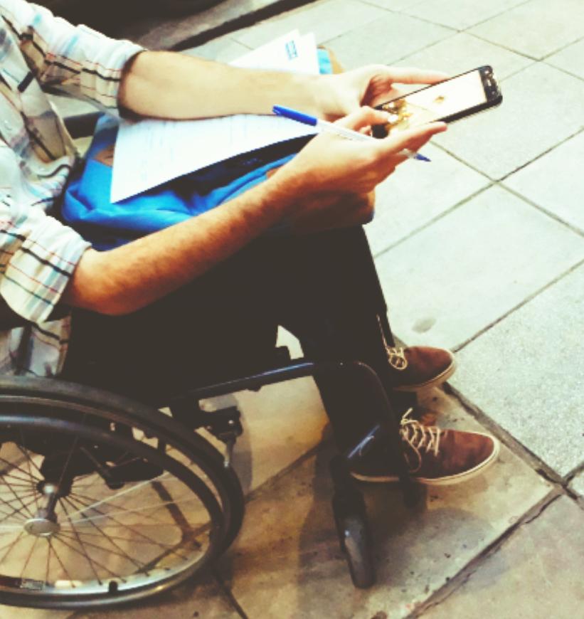 La imagen muestra una persona en silla de ruedas con un celular y una lapicera en las manos, y una mochila y apuntes en el regazo. El plano sólo muestra parcialmente la figura, del torso para abajo.