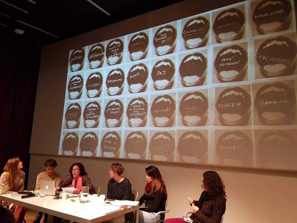 La imagen muestra la mesa de debate realizada en Fundación Proa con una proyección de una serie de fotografías de fondo.