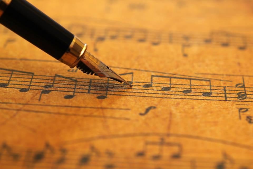 La imagen muestra una pluma fuente escribiendo una partitura.