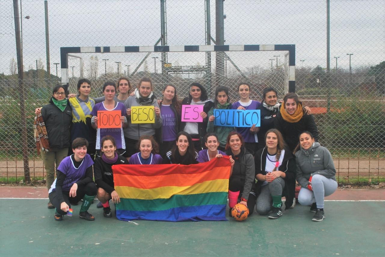 """La imagen muestra a los equipos de fútbol femenino de Filo:UBA y Sociales con una bandera LGBT y carteles con la consigna """"Todo beso es político""""."""