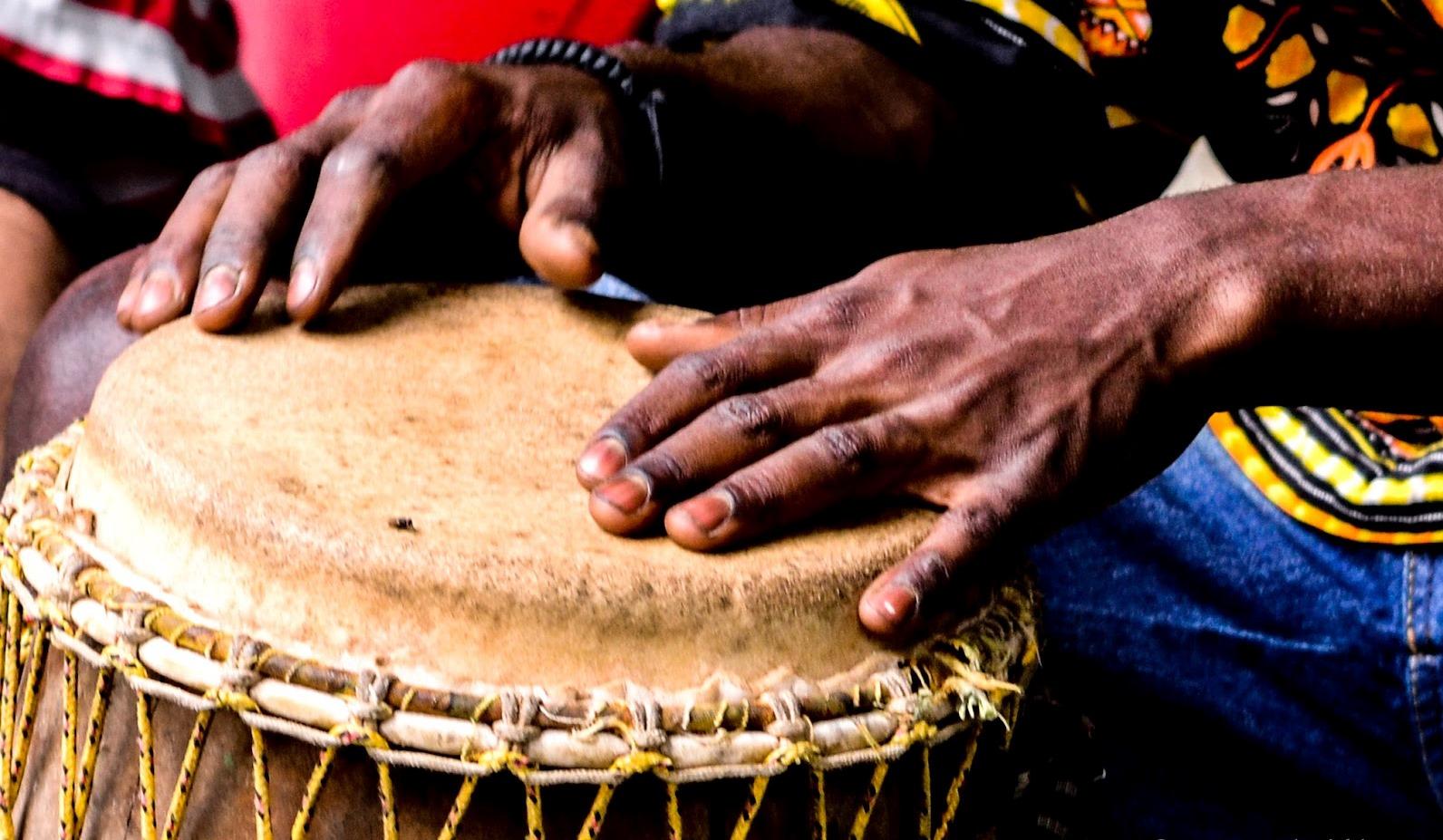 La imagen muestra dos manos tocando un tambor afro-brasileño.